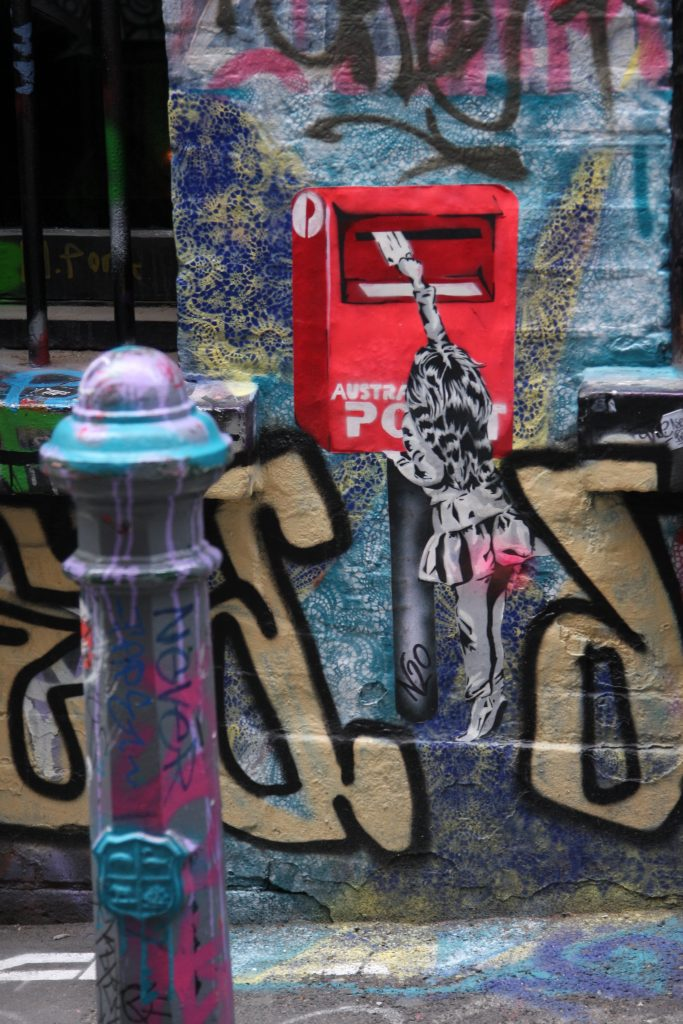 graffiti on a building wall showing a little girl posting a letter in an Australian Post letter box