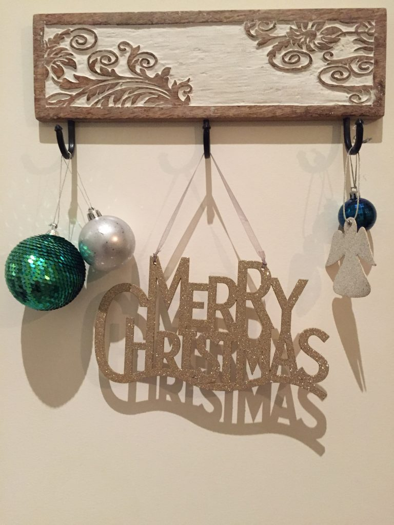 Christmas decorations hanging on hooks decorating a bedroom door