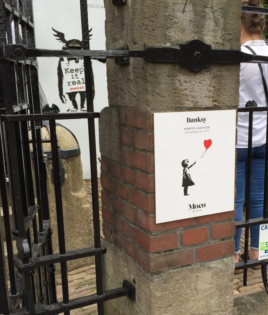 Moco Museum Banksy little girl with a heart balloon sign on the fence post outside of the museum in Amsterdam