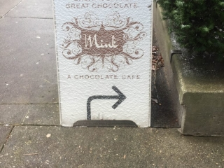 Mink Chocolates Vancouver Folding Street Sign lightly covered with snow