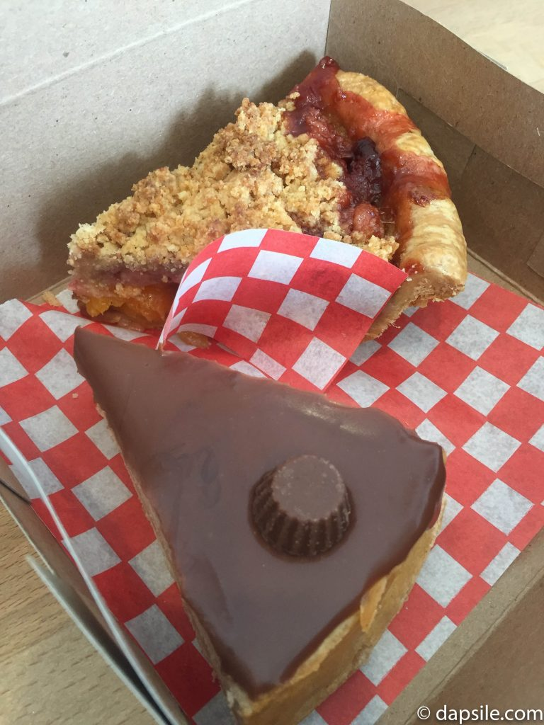 Peanut Butter Cup Cheesecake and Strawberry Mango Crumb in takeaway box from the Half Baked Cookie Company