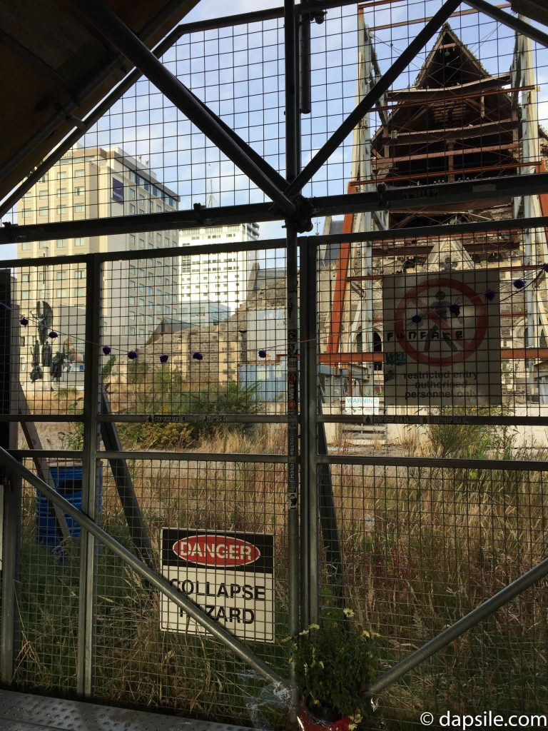 damaged Christchurch Cathedral through the fence with warning sign