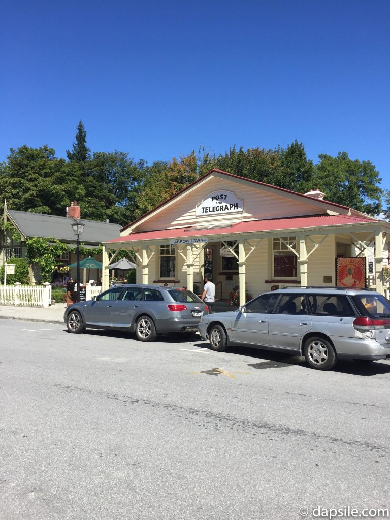 cars parked in front of the Arrowtown post office located in a historical building