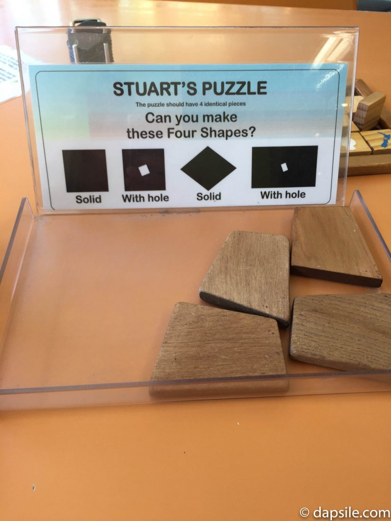 Puzzling World Puzzle called Stuart's Puzzle with different wooden blocks that you have to make shapes with