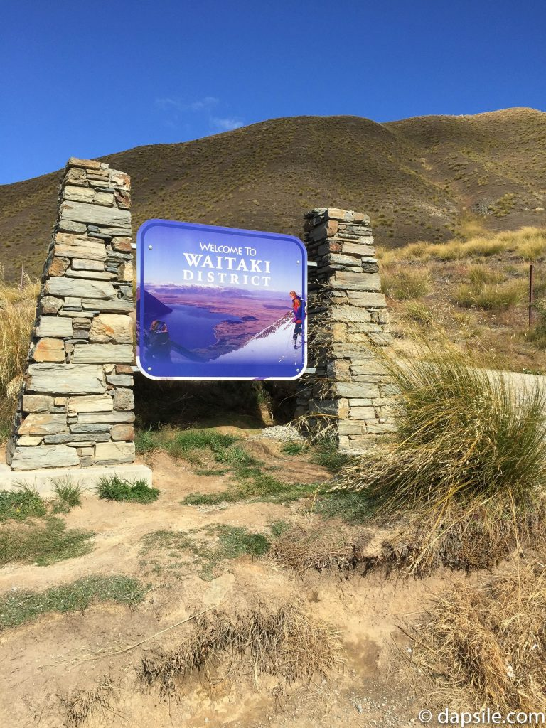 Welcome to Waitaki District sign in NZ on the side of the road with mountains in the background