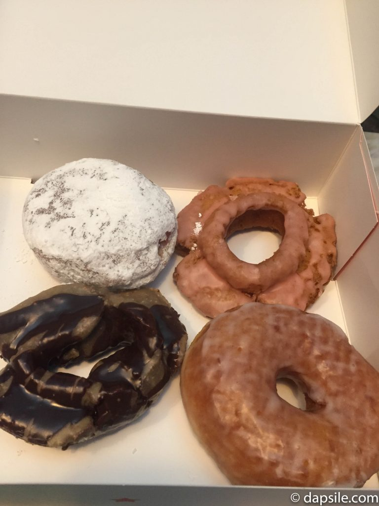 Four of the Lucky's Doughnuts I tried in a togo box
